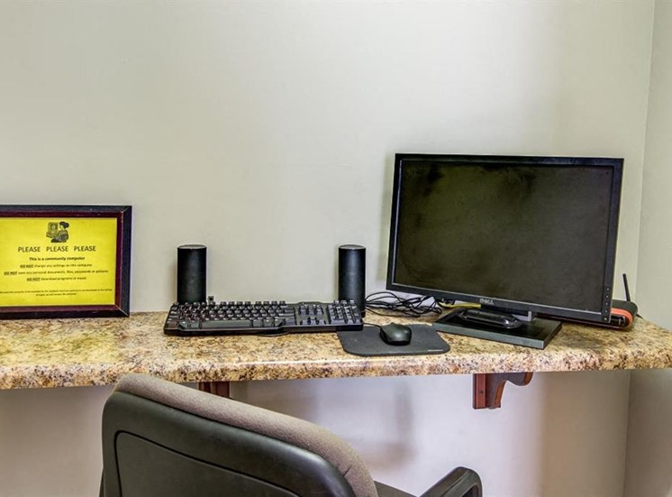 Business Center with Computer Next to Keyboard and Speakers Next to Yellow Sign
