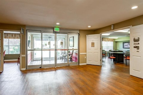 Spacious Entryway Into Community Center with Large Doors Next to Lounge Area with Tables and Chairs
