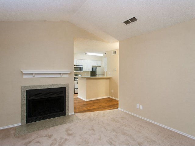 Living room with fireplace, white mantle above fireplace, peach colored walls, and view of fully equipped kitchen