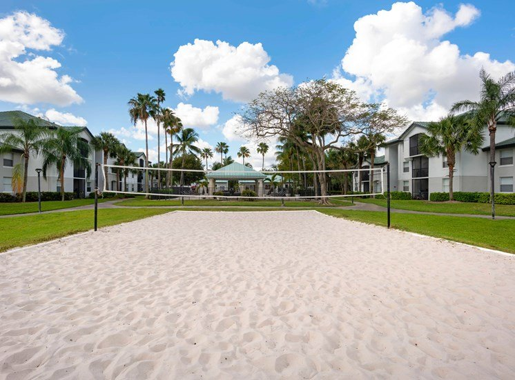 Sand Volleyball Court Surrounded by Trees with Building Exterior in The Background