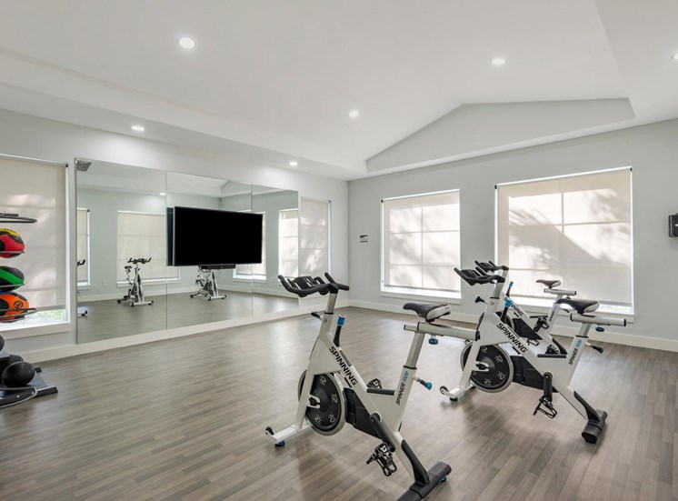Bright Fitness Center with Covered Windows, Exercise Equipment and Mirrored Accent Wall with Mounted TV  Next to French Glass Doors