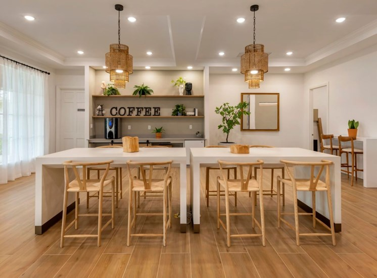Community room table with eight chairs, table decor, kitchen area with coffee, fridge and shelves