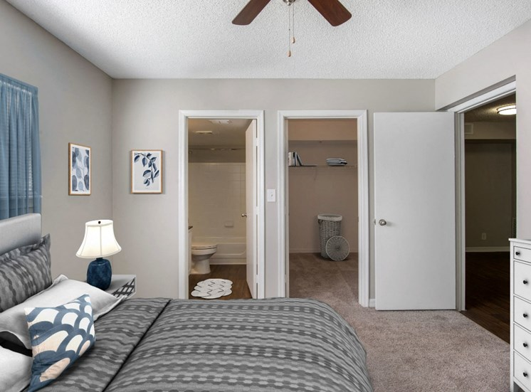 Virtual staged Master Bedroom with large bed, nightstand, dresser, walkin closet, ceiling fan and wall decor