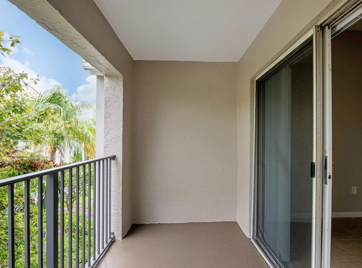 Apartment home balcony with sliding glass door, metal railing overlooking mature trees