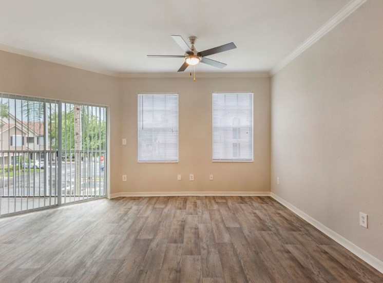 Spacious living room with hardwood style flooring, multi speed ceiling fan, large window and private balcony access
