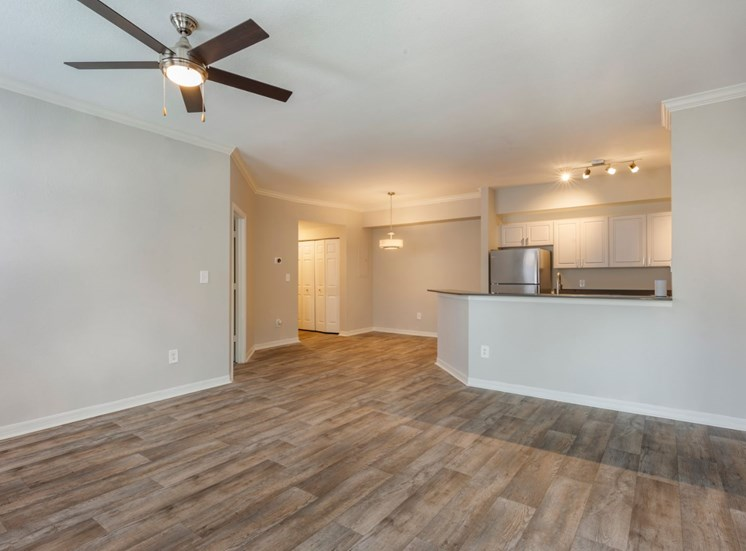 Living room with hardwood style flooring, and kitchen in the background