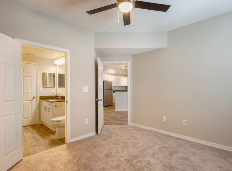 Spacious bedroom with carpet flooring, multi speed ceiling fan, and in-suite bathroom