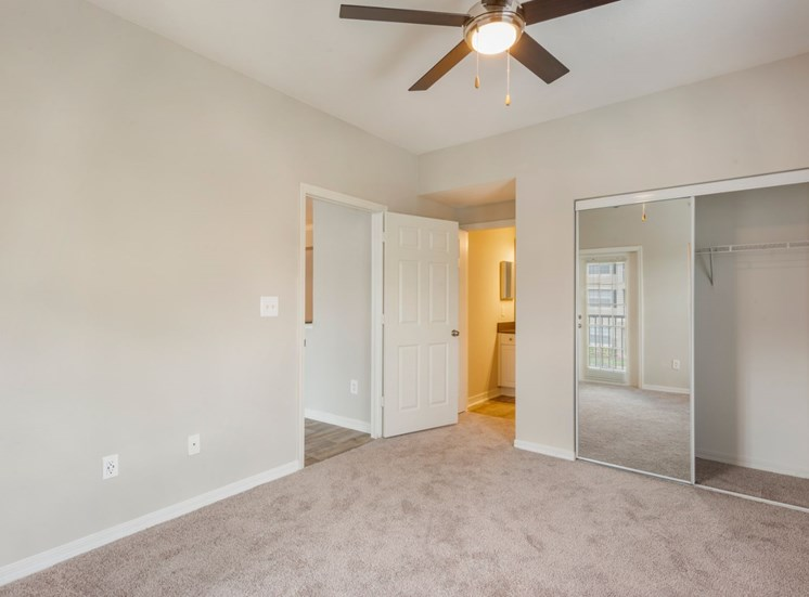 Bedroom with carpet flooring, in suite bathroom, large closet and multi speed ceiling fan