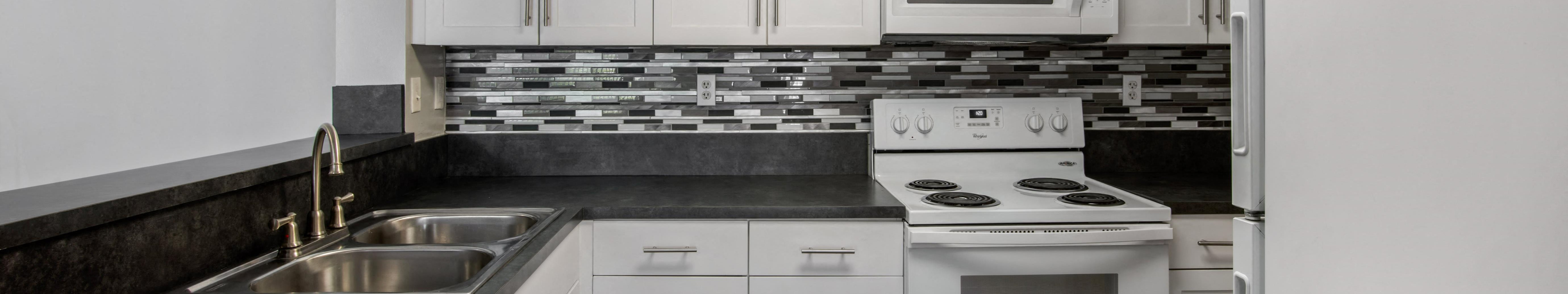Model Kitchen with White Appliances,  White Cabinets, Black Counters and Glass Backsplash