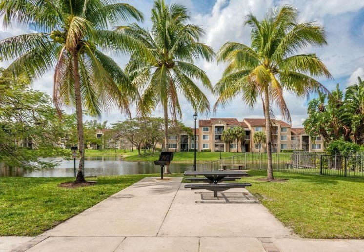 Picnic area with bbq grills, picnic table and palm trees next to lake