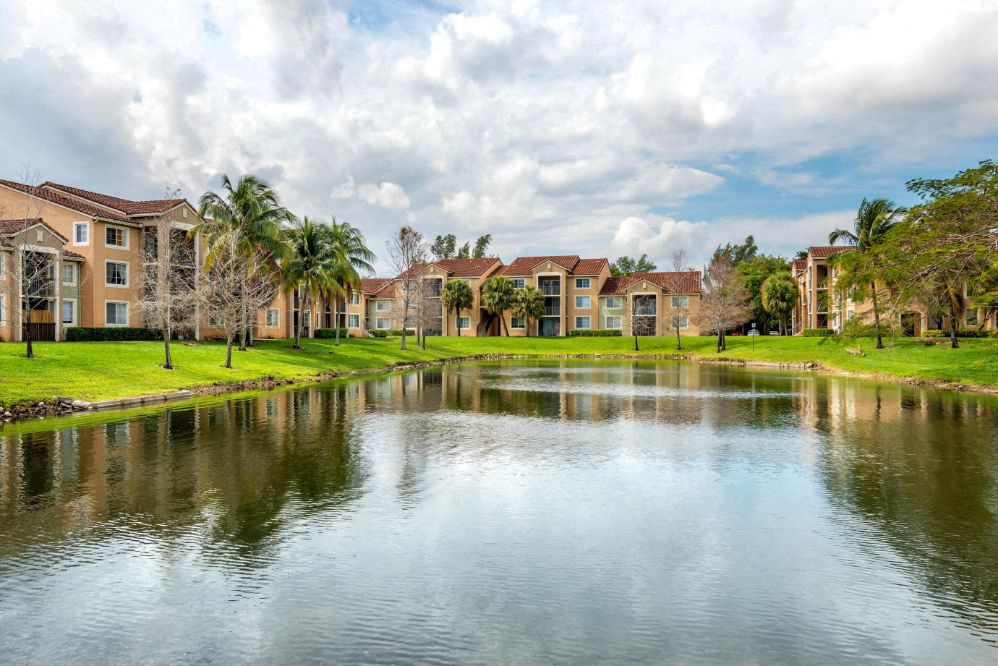 Lake view surrounded by grass area, mature trees and building exteriors