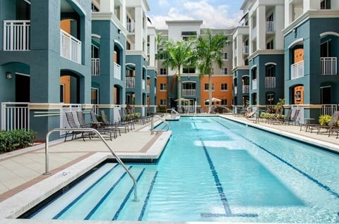 Swimming Pool with lap lanes and exterior of apartment building, patios and balconies in view
