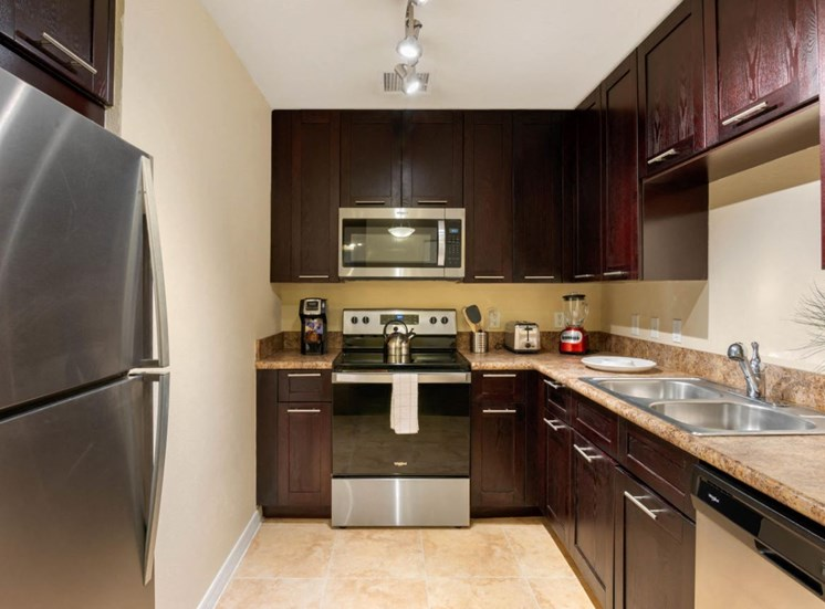 Kitchen with espresso cabinetry, fully equipped with a stove, microwave, refrigerator, and double basin sink