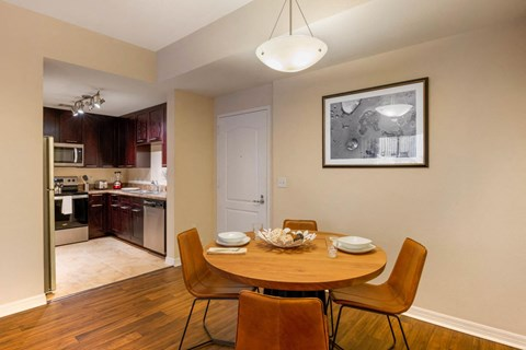 Dining room with access to the kitchen with a dining room table, four chairs, a framed photo, and hardwood style flooring