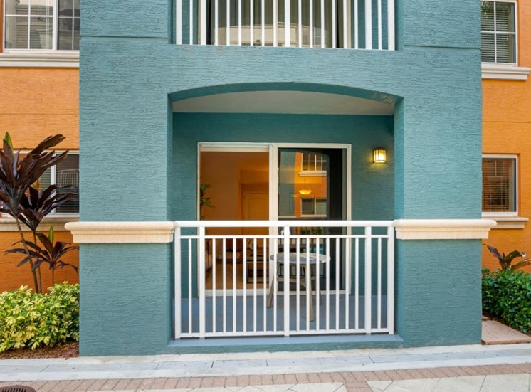 View of apartment exterior painted blue and orange and native landscaping