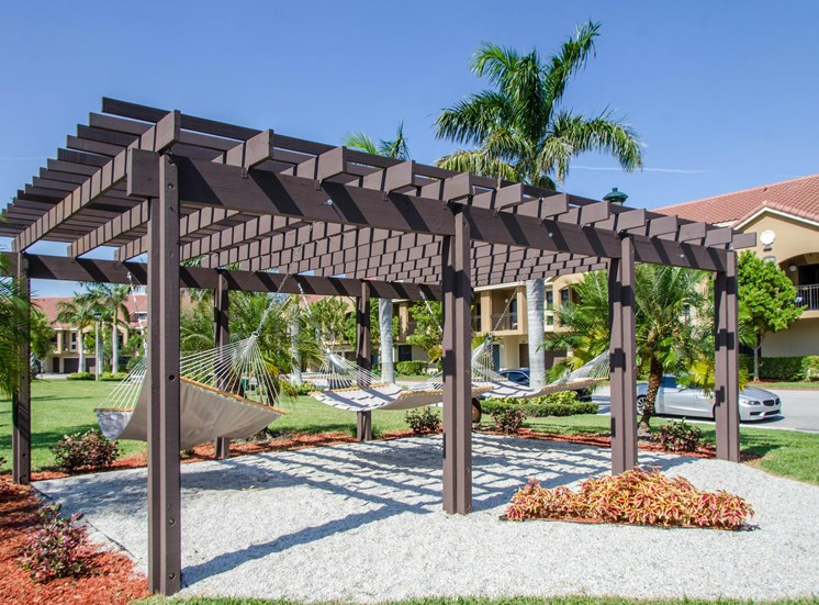 Hammock park covered with a pergola and fresh landscaping