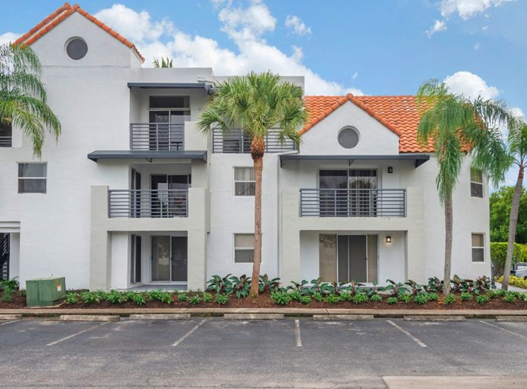 Sheridan Ocean Club Apartments  Building Exterior with parking lot and palm trees