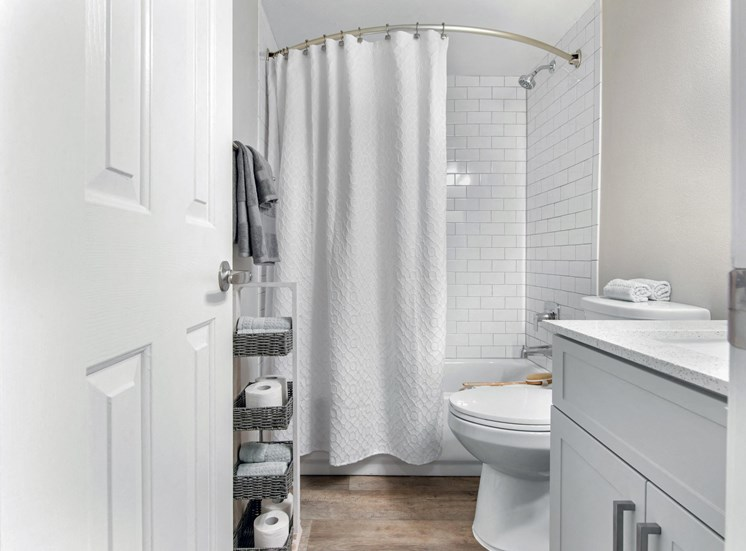 Bathroom with wood style flooring, white cabinets and countertops, white shower tiles in bathtub and stand up shower, white shower curtain, bathroom stand up organizer with baskets and hanging towels