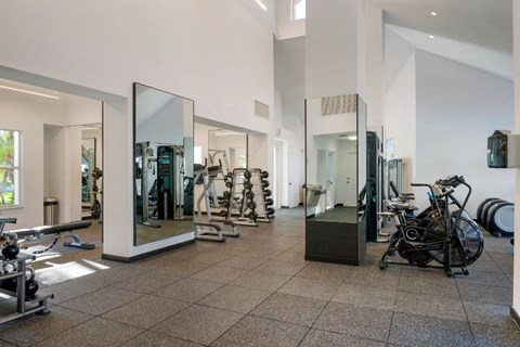 Fitness center with mirrors, free weights, and bicycles