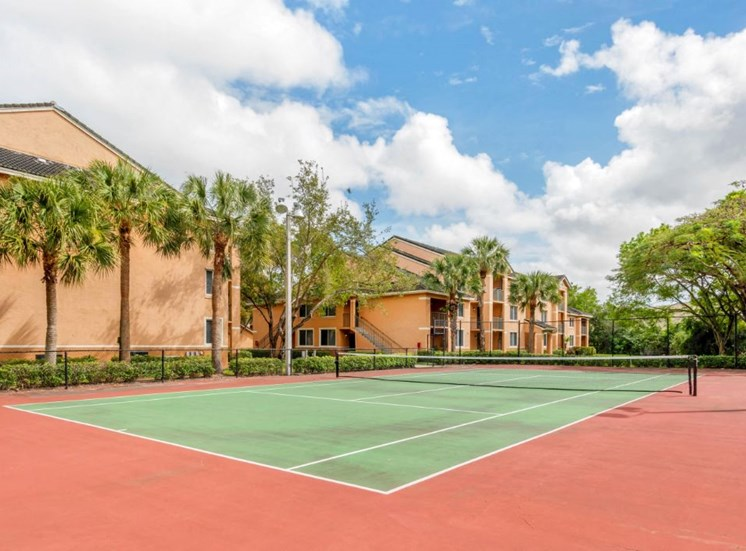 Tennis court with palm trees and building exteriors