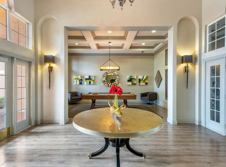 Leasing office entrance with large table, table flowers and pool table