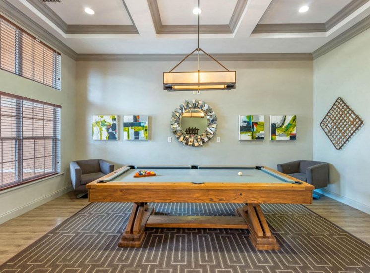 Pool table with two chairs and wall decor