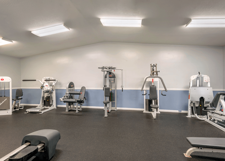 Fitness center with various weight machines spaced out on a rubber flooring and vaulted ceilings