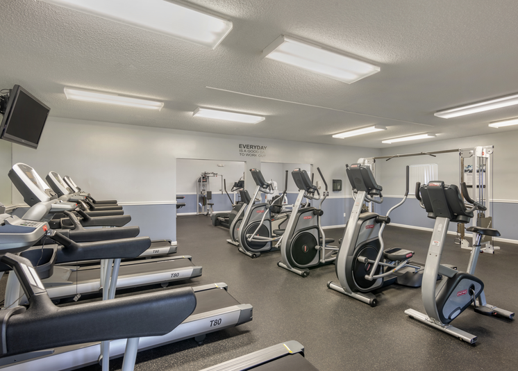 Fitness center with various treadmills and stationary bikes spaced out on a rubber flooring and vaulted ceilings