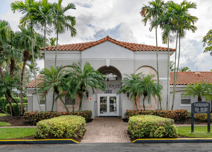 Exterior entrance to leasing office with brick walkway surrounded by bushed, palm trees and green grass