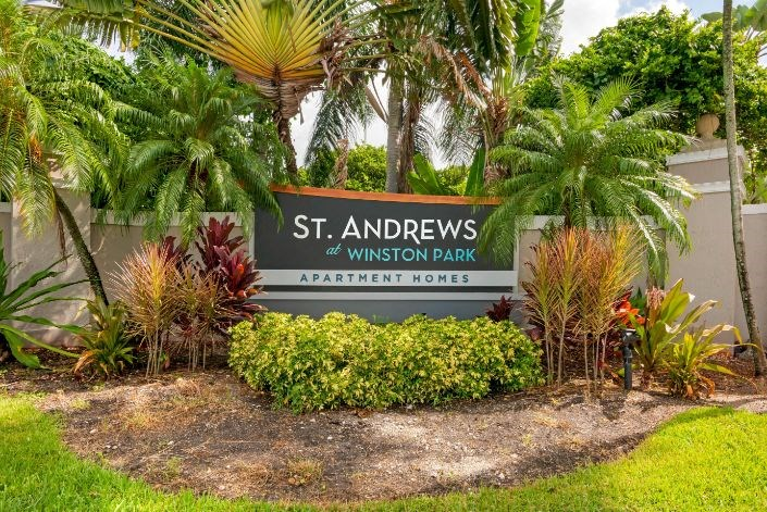 Front entrance sign surrounded by plants, flowers and palm trees