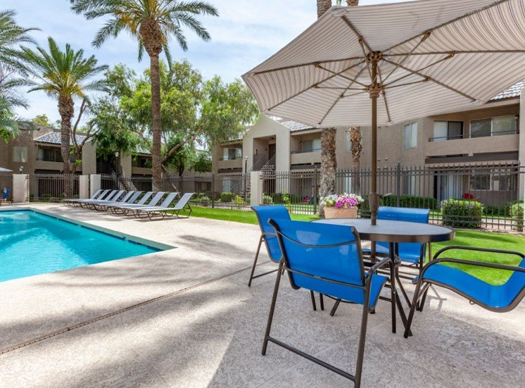 Poolside Picnic Table with Umbrella with Building Exteriors in the Background