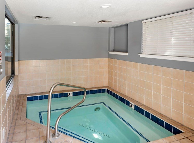 Indoor heated spa with half tiled wall and half grey wall