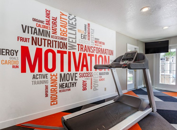 Fitness Center with Treadmill Next to Motivational Word Mural