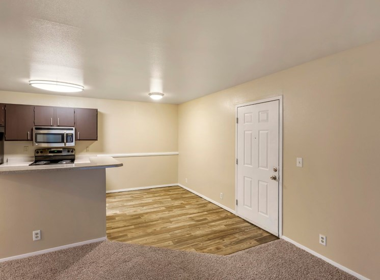 Apartment entry, dining room and kitchen with hardwood flooring, breakfast bar, and cabinetry