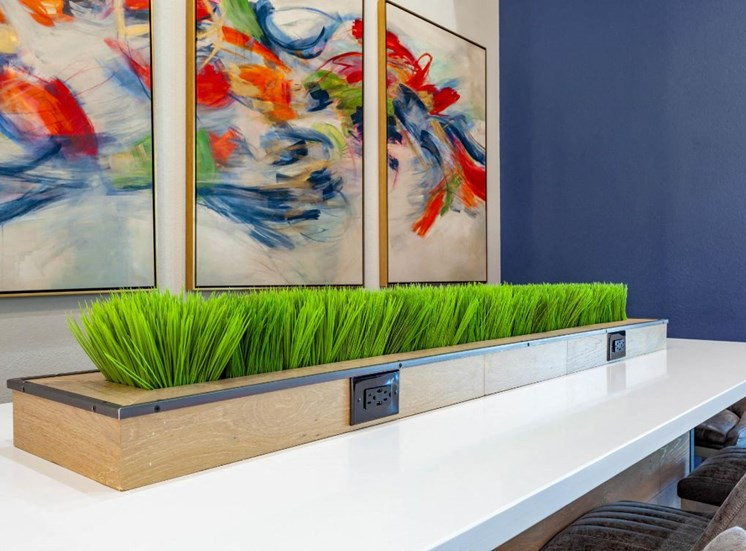 Clubhouse Table with Charging Station in Decorative Plant Centerpiece Next to Wall Art