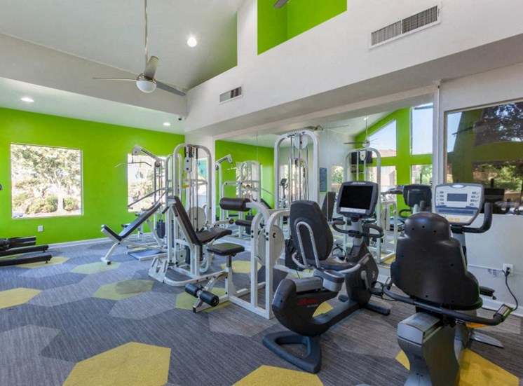 Bright Fitness Center with Lime Green Accents, Mirror Accent Wall and Exercise Equipment
