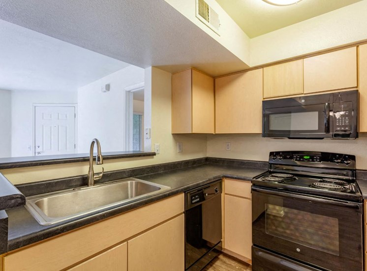 Fully Equipped Kitchen with Blonde Cabinets, Grey Counters and Black Appliances