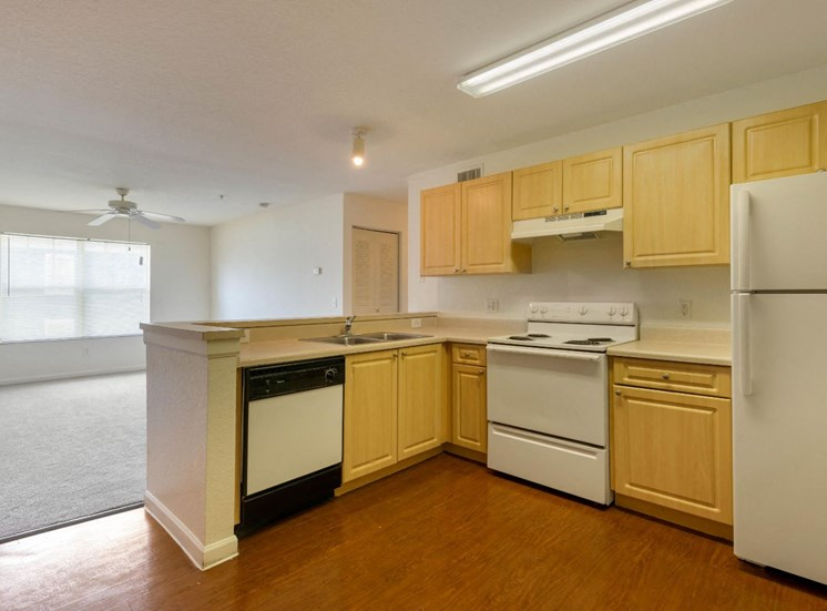 Kitchen light brown cabinets, wood style flooring and white appliances