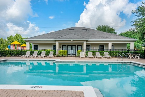 Leasing Office Exterior with Swimming Pool and Sun Deck with Lounge Chairs with Playground and Treeline in the Background