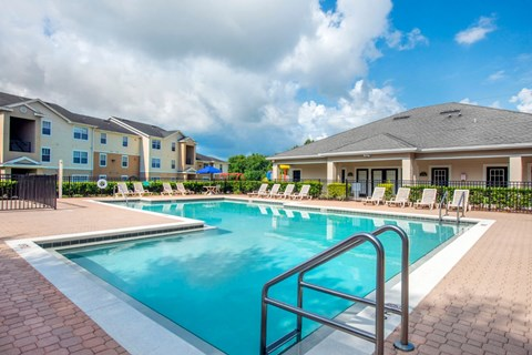 Leasing Office Exterior with Swimming Pool and Sun Deck with Lounge Chairs with Playground and Building Exterior in the Background