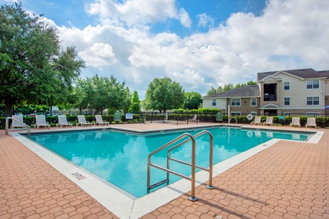 Leasing Office Exterior with Swimming Pool and Sun Deck with Lounge Chairs with Treeline in the Background
