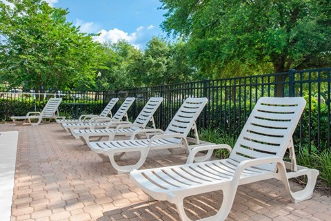 Lounge Chairs on Sun Deck Near Fence  with Treeline in the Background