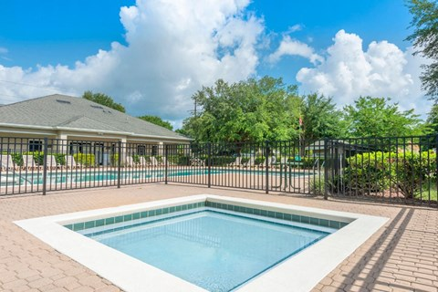 Fenced in Wading Pool Wading with Leasing Office Exterior Swimming Pool and Treeline in the Background