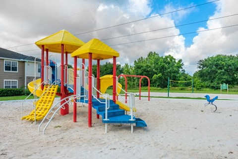 Colorful Playground on Sand Next to Sand Volleyball Court  Separated by Grass with Treeline and Building Exterior in the Background