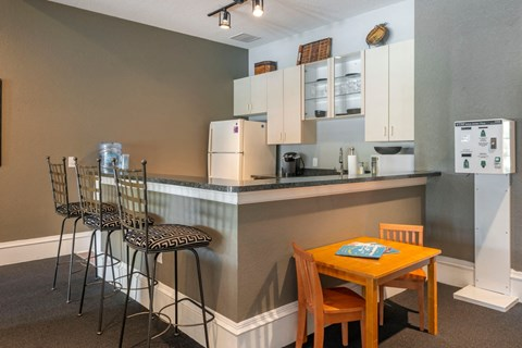 Clubhouse Kitchen with Barstools a Miniature Table and Chairs and White Appliances Cabinets
