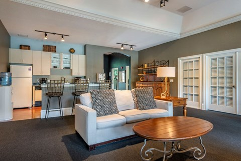 Clubhouse Kitchen with White Cabinets in the Background of Seating Area with White Couch with Throw Pillows and Wooden Coffee Table