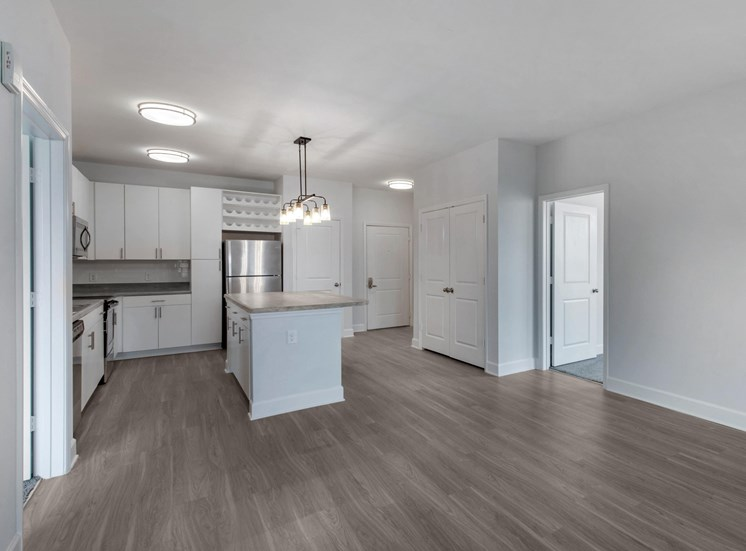 Hardwood Style Flooring From Living Room Showing Kitchen with White Cabinets
