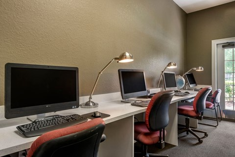 Computer Lab with White Counters Desk Lamps and Red Rolling Chairs
