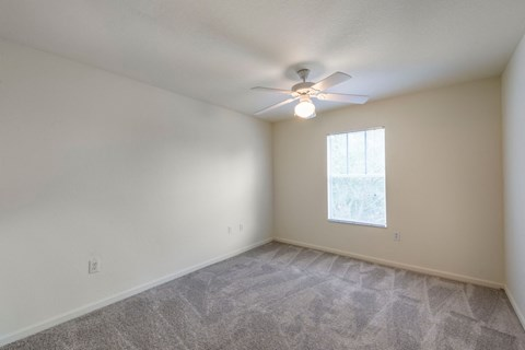 Carpeted Bedroom with Window and White Ceiling Fan