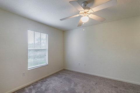 Carpeted Bedroom with White Ceiling Fan and Window